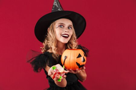Photo of positive evil little girl witch in carnival halloween costume isolated over red wall background holding holiday pumpkin candy box bag.