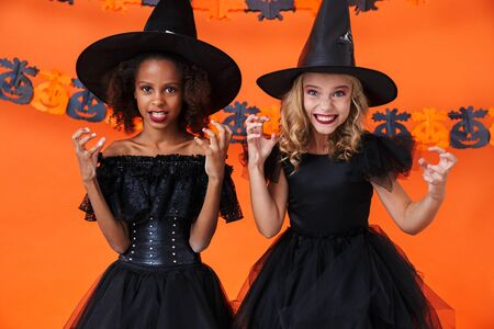Image of amusing multinational girls in black halloween costumes scratching and frightening isolated over orange pumpkin wall