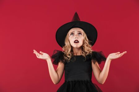 Photo of confused little girl witch in carnival halloween costume isolated over red wall background. Zdjęcie Seryjne