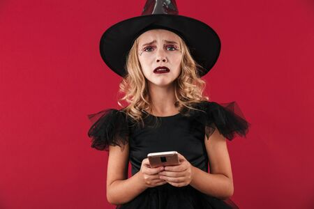 Upset little girl wearing Halloween witch costume standing isolated over red background, using mobile phone