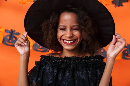 Image of joyful african american girl in black halloween costume laughing with eyes closed isolated over orange pumpkin wall
