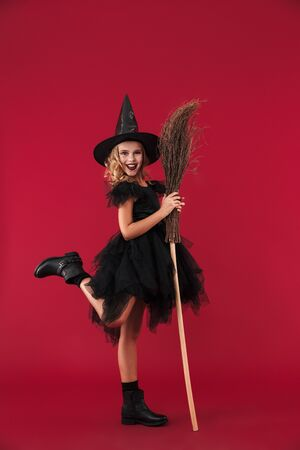 Image of cheery little girl witch in carnival halloween costume isolated over red wall background with broom. Zdjęcie Seryjne
