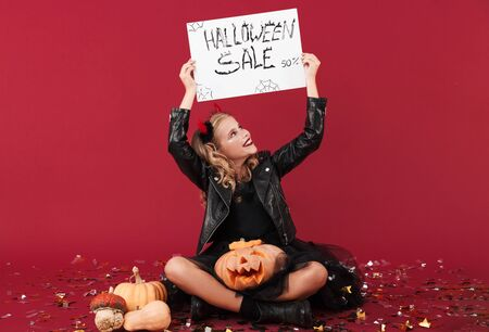 Picture of smiling optimistic pleased little girl devil in carnival halloween costume isolated over red wall background holding pumpkin and copyspace blank with sale text. Zdjęcie Seryjne
