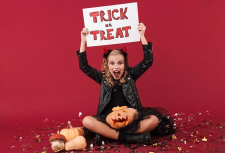 Picture of positive screaming little girl devil in carnival halloween costume isolated over red wall background holding pumpkin and copyspace blank with trick or treat text. Zdjęcie Seryjne