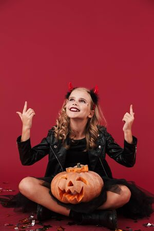 Picture of cute positive optimistic little girl devil in carnival halloween costume isolated over red wall background holding pumpkin pointing aside.