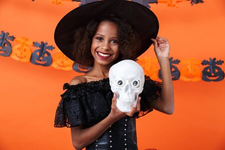 Image of nice african american girl in black halloween costume holding toy skull and smiling isolated over orange pumpkin wall