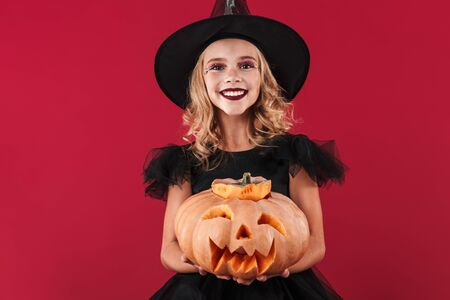 Photo of positive optimistic smiling little girl witch in carnival halloween costume isolated over red wall background holding pumpkin.