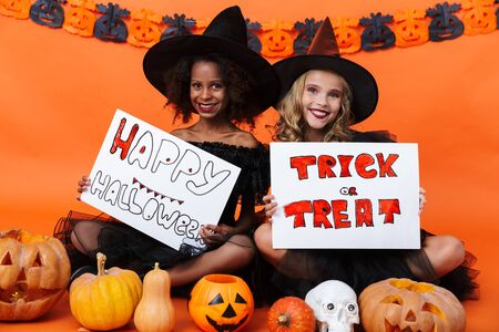 Image of smiling multinational girls in black halloween costumes holding placards while sitting on floor isolated over orange pumpkin wall