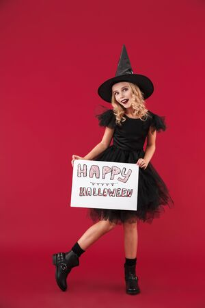 Photo of smiling cheery little girl witch in carnival halloween costume isolated over red wall background holding copyspace blank with halloween text.