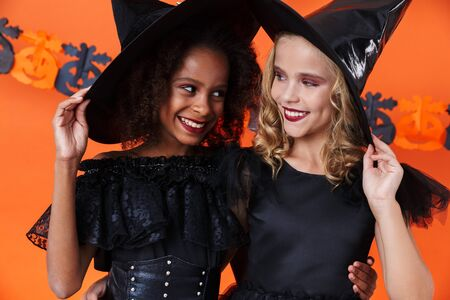 Image of lovely witch girls in black halloween costumes smiling and hugging together isolated over orange pumpkin wall Zdjęcie Seryjne