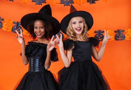 Image of nice witch girls in black halloween costumes smiling and gesturing peace sign isolated over orange pumpkin wall Фото со стока