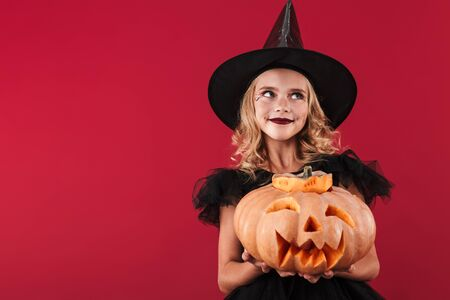 Photo of dreaming thinking smiling little girl witch in carnival halloween costume isolated over red wall background holding pumpkin. Imagens