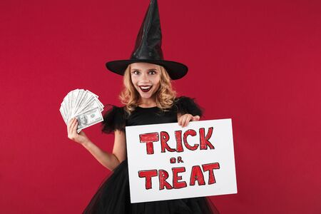 Photo of positive happy little girl witch in carnival halloween costume isolated over red wall background holding copyspace blank with trick or treat text and money.