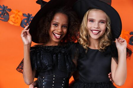Image of amusing witch girls in black halloween costumes smiling and hugging together isolated over orange pumpkin wall Zdjęcie Seryjne