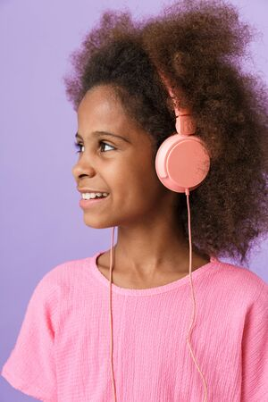 Image of a positive optimistic happy young african girl kid posing isolated over purple wall background listening music with headphones.