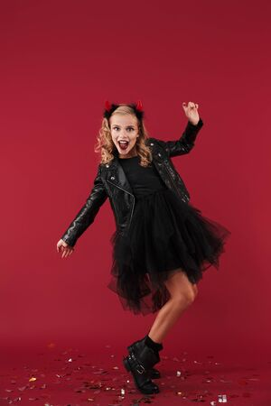 Picture of positive happy little girl devil in carnival halloween costume isolated over red wall background.