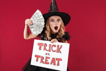 Photo of surprised shocked little girl witch in carnival halloween costume isolated over red wall background holding copyspace blank with trick or treat text and money. Zdjęcie Seryjne