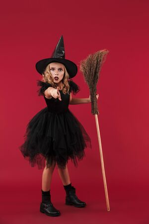 Picture of confused little girl witch in carnival halloween costume isolated over red wall background with broom pointing to you. Zdjęcie Seryjne