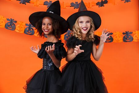 Image of nice multinational girls in black halloween costumes smiling and making fun isolated over orange pumpkin wall Zdjęcie Seryjne