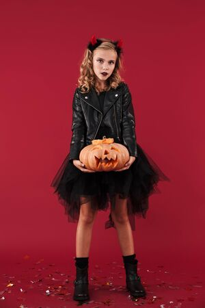 Picture of serious little girl devil in carnival halloween costume isolated over red wall background holding pumpkin.