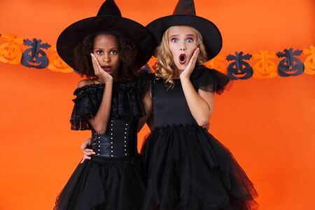 Image of shocked multinational girls in black halloween costumes hugging and looking at camera isolated over orange pumpkin wall