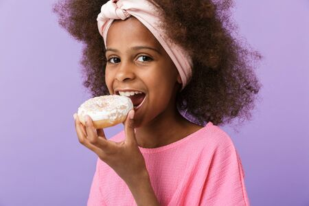 Image of a cute optimistic young african girl kid posing isolated over purple wall background eat donut. Reklamní fotografie - 138202163