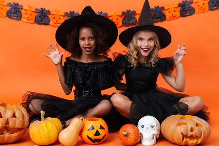 Image of happy multinational girls in black halloween costumes scratching while sitting with pumpkins and toy skull isolated over orange pumpkin wall