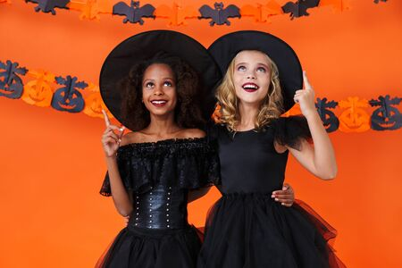 Image of smiling multinational girls in black halloween costumes hugging and pointing fingers upward isolated over orange pumpkin wall Zdjęcie Seryjne