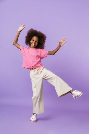 Image of a cheery young pleased african girl kid posing isolated over purple wall background.