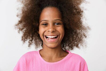 Bild eines glücklichen lachenden jungen afrikanischen Mädchenkindes, das lokalisiert über weißem Wandhintergrund aufwirft.