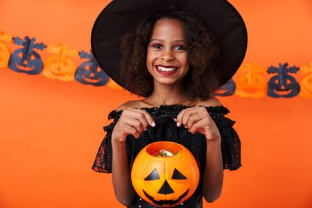 Image of happy african american girl in black halloween costume smiling and holding toy pumpkin isolated over orange wall Zdjęcie Seryjne