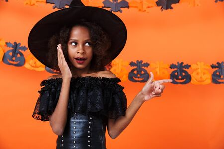 Image of excited african american girl in black halloween costume pointing finger aside isolated over orange pumpkin wall Zdjęcie Seryjne