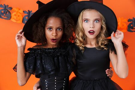 Image of beautiful witch girls in black halloween costumes looking at camera in wonder isolated over orange pumpkin wall Фото со стока