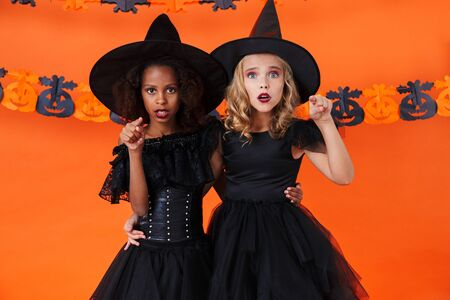 Image of confused multinational girls in black halloween costumes hugging and pointing fingers at camera isolated over orange pumpkin wall