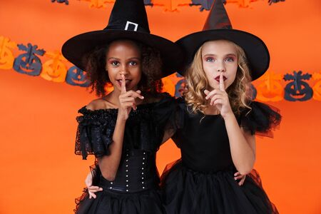 Image of multinational witch girls in black halloween costumes showing silence gesture isolated over orange pumpkin wall Zdjęcie Seryjne