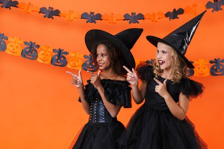 Image of smiling multinational girls in black halloween costumes hugging and pointing fingers aside isolated over orange pumpkin wall Zdjęcie Seryjne