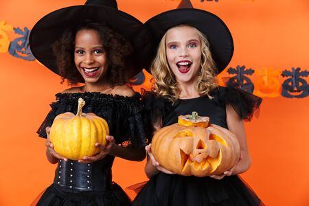 Image of laughing multinational girls in black halloween costumes holding pumpkins isolated over orange wall Reklamní fotografie - 138202043