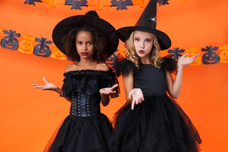 Image of confused multinational girls in black halloween costumes looking at camera isolated over orange pumpkin wall