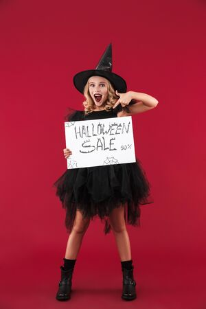 Image of positive emotional little girl witch in carnival halloween costume isolated over red wall background holding copyspace blank with sale text. Reklamní fotografie - 138201608