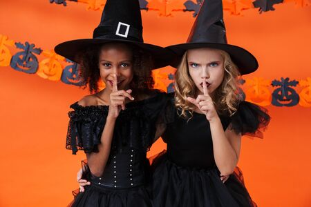 Image of multinational pretty girls in black halloween costumes showing silence gesture isolated over orange pumpkin wall