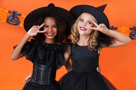 Image of lovely witch girls in black halloween costumes smiling and gesturing peace sign isolated over orange pumpkin wall