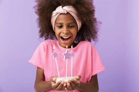 Image of a happy optimistic positive young african girl kid posing isolated over purple wall background holding birthday cake with candles. 写真素材