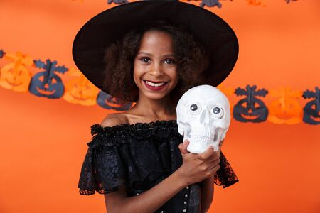 Image of joyful african american girl in black halloween costume holding toy skull and smiling isolated over orange pumpkin wall