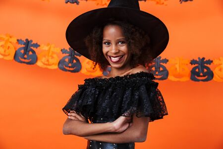 Image of funny african american girl in black halloween costume looking at camera and smiling isolated over orange pumpkin wall
