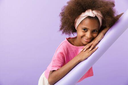 Image d'une jeune fille africaine heureuse joyeuse et optimiste posant isolée sur fond de mur violet.