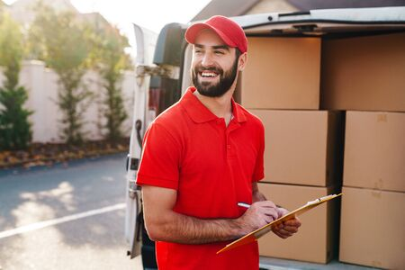 Image of smiling delivery man in red uniform holding clipboard and writing near car with parcel boxes outdoors