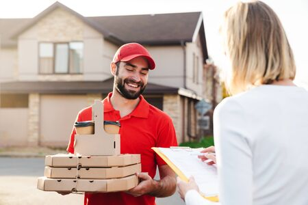 Image of smiling delivery man in red uniform giving food order to caucasian woman at city street Reklamní fotografie