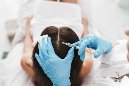 Photo of woman getting mesotherapy treatment in head for stimulation of growing hair by specialist in beauty salon