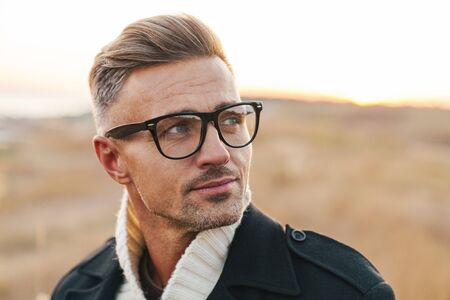 Image of a concentrated handsome mature man walking outdoors at the nature wearing eyeglasses.