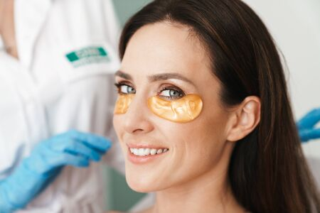 Photo of happy woman getting cosmetic procedure with patches by specialist in beauty salon